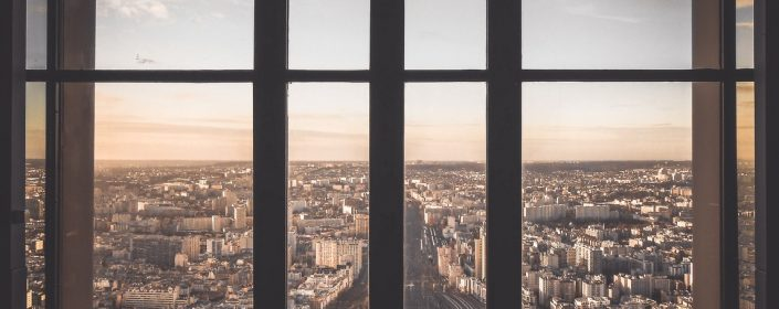 View of a city from a set of broad, modern windows.