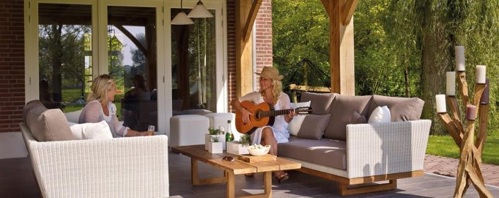 Two women site on a patio with the doors closed behind them, with one woman playing guitar.