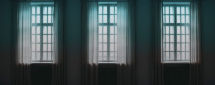 Inside a dark empty living room facing three large windows with drapes hung to the floor