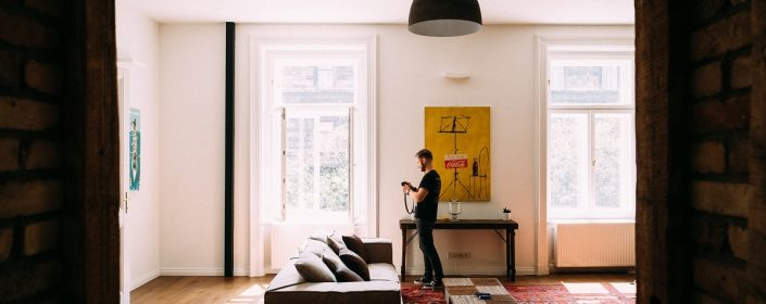 Man stands in his flat next to two bright, clean windows in the spring.