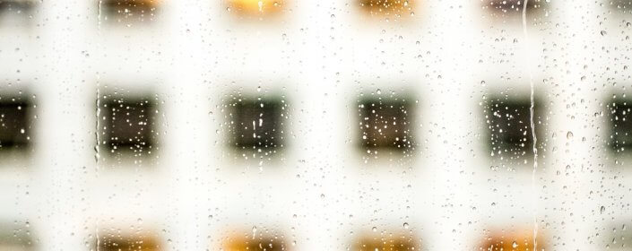 Window with rain on it looking out to another building